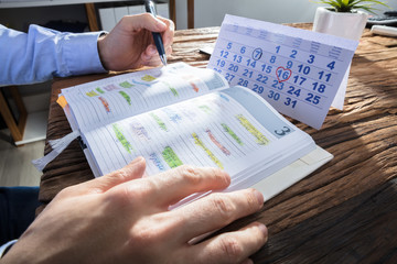 Fototapete - Businessperson's Hand Checking Schedule In Diary