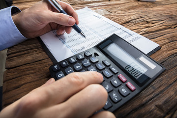Businessman's Hand Calculating Financial Data With Calculator