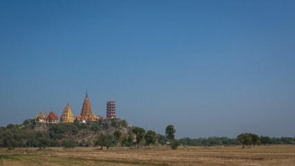 paddy field and Thai temple on mountain at Kanchanaburi province Thailand