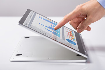 Man Pointing At The Business Graph On Hybrid Laptop