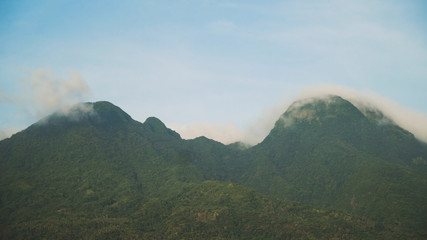 Mountains landscape, rainforest, jungle, blue sky, clouds and mist. Volcano on the island of Camiguin. Travel concept.