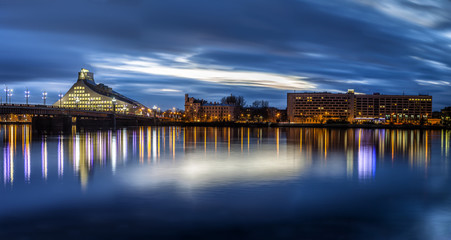 Riga skyline with National Library. Night shot with scenic water reflections in Daugava river waters