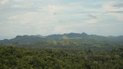 Vew Mountains with rainforest covered with green vegetation and trees on the tropical island, landscape. Mountains and hills with wild forest, sky clouds. Hillside rainforest and jungle. Philippines
