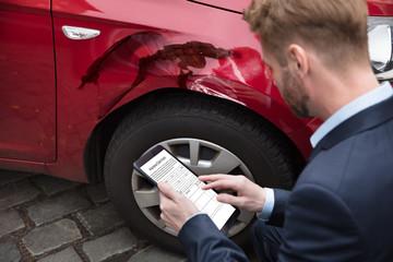 Man Looking At Digital Tablet Near Car