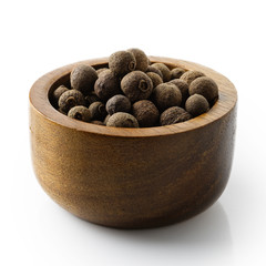 Whole allspice in dark wood bowl isolated on white.