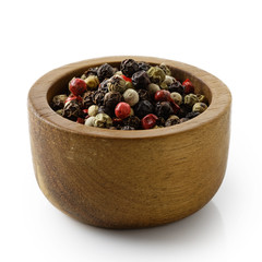 Mixed peppercorns in dark wood bowl isolated on white.
