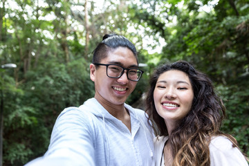 Asian Couple Taking a Selfie in the Park