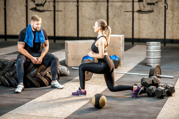 Young woman squatting before the training with man trainer in the crossfit gym