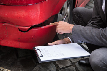 Insurance Agent Writing On Clipboard After Car Accident