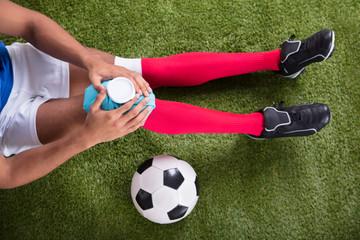 Injured Soccer Player Applying Ice Pack On Knee