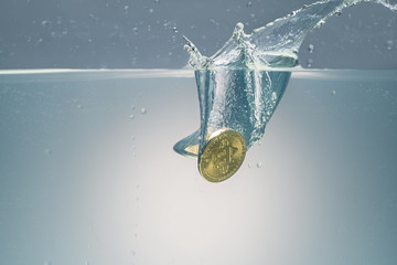 Golden bitcoin being dropped into water shot