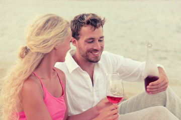 Couple drinking rose wine on romantic sunset beach picnic for valentines day. Caucasian young man and blonde woman relaxing enjoying date dating on summer holiday.
