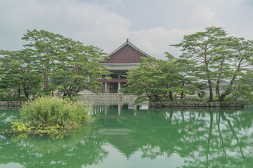One of the palaces surrounded by water, with a reflection of the rooftop and trees, in Gyeongbokgung Palace, Seoul, South Korea