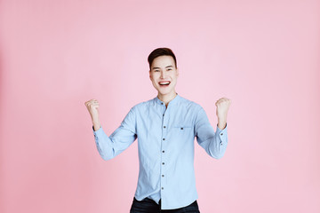 Studio shot of positive excited young man clenching fists and screaming, celebrating his victory or success. Life achievement, goals and happiness concept. pink background.Copy space.