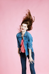 body language and emotions. Studio shot of happy young fair-haired woman  dressed casually jeans and pink t-shirt. pink background. girl smiles, laughs and looks in the camera. flying hair. copy space