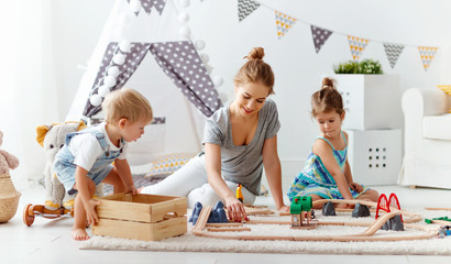 family mother and children play a toy railway in   playroom