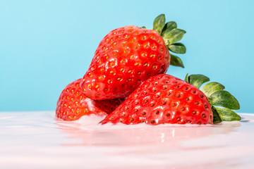 Strawberry close-up in pink yogurt on blue background