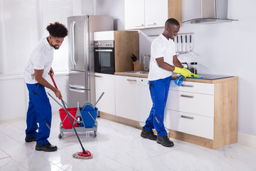 Smiling Two Young Male Janitor Cleaning The Kitchen
