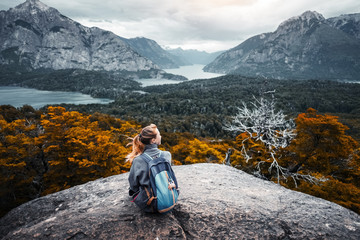 Woman hiker sits and enjoys valley view from viewpoint. Hiker reached top of the mountain and relaxes. Patagonia, Argentina