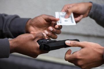 Hands Exchanging Handgun For Banknote