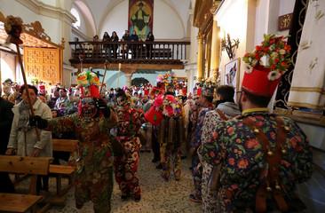 "Believers dressed as ""diablos"" (devils), dance inside church before a procession during the ""Endiablada"" festival in Almonacid del Marquesado"