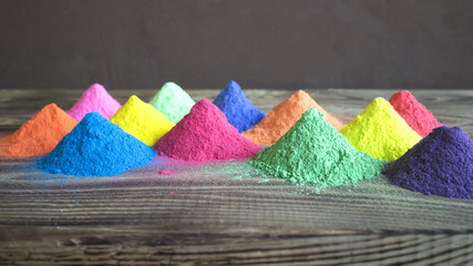 Bright colors for holi festival. Colorful holi paint in the form of pyramids on a wooden brown table  with copy space. Natural organic pigment.