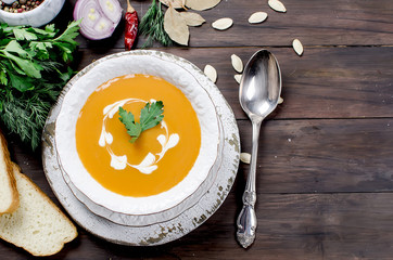 Pumpkin cream soup with pumpkin seeds  in white plate
