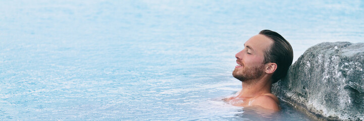 Wellness Spa man relaxing in hot springs outdoor at luxury resort spa retreat. Handsome young male model with eyes closed resting in natural water pool on travel vacation holiday. banner background.