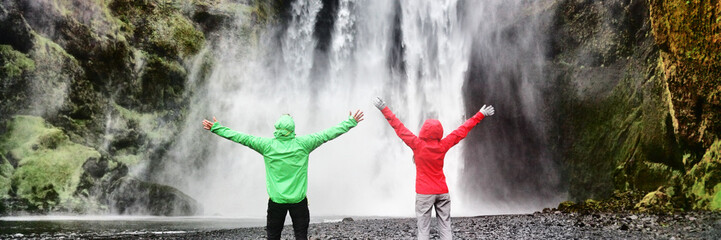 Adventure travel in amazing nature landscape. Couple tourists enjoying freedom on vacation at waterfall banner panorama . People with open arms in success, summer holiday in Iceland.