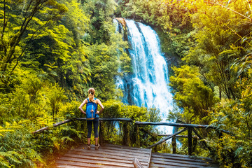 Woman hiker enjoys waterfall view from viewpoint surrounded by lush forest and vegetation. Chile
