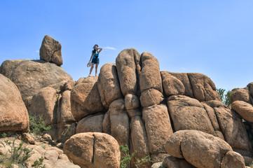 Eine junge Touristin auf einem Felsen in der Wüste Gobi, Mongolei