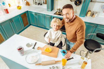 Healthy food. Top view of nice positive father and son standing together in the kitchen and looking at you while preparing food