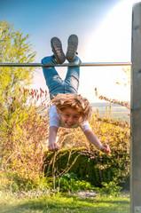 Fröhliches Kind turnt an einer Reckstange, ist draußen und zeigt gesundes Selbstbewusstsein