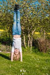 Fröhliches Mädchen turnt draußen einen Handstand und zeigt Balance und Zufriedenheit