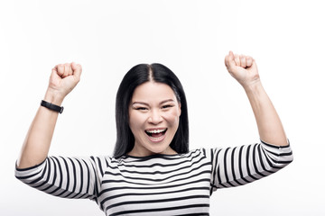 Great success. Charming cheerful young woman in a striped pullover raising her hands joyfully and smiling brightly while posing isolated on a white background