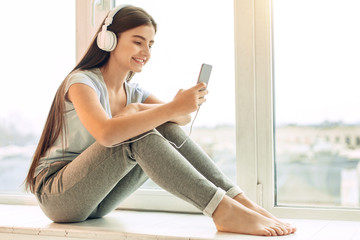 Nice music. Charming teenage girl with long hair sitting on the window sill and listening to the music in the headphones while choosing the next song with smile