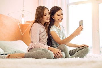 Precious moment. Adorable teenage girls sitting on the bed and taking selfies together while smiling cheerfully at the camera