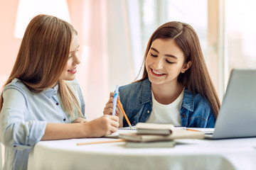 Vital help. Pleasant teenage girl sitting at the table next to her younger sister and helping her with a home assignment while smiling
