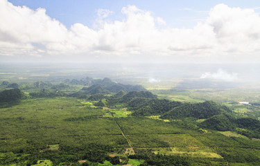 Large hills and burning fields are seen from the air during an aerial survey in central Belize.