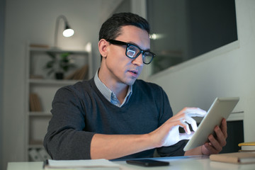 Try this way. Attractive good looking male programmer holding tablet while looking at the screen and working