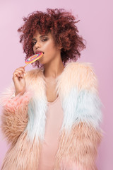 Fashionable afro woman with lollipop on pink background.
