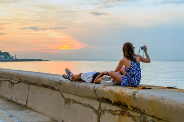 Young couple watching and photographing the sunset on the ocean