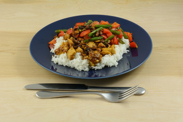 Spicy chicken and vegetables dish over rice on blue plate with fork and knife