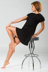 Profile of Beautiful Woman Leaning on a Stool