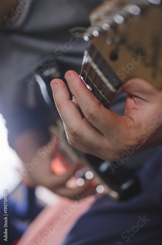 Musician hands playing chords on electric guitar\
