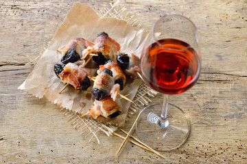 Leckere Tapas: Getrocknete Pflaumen in Speck gerollt und gebraten, dazu ein Glas Old Tawny Portwein – Delicious Spanish tapas:  Fried prunes wrapped in bacon served with Portuguese port wine