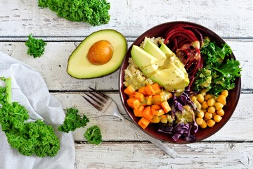 Buddha bowl with quinoa, avocado, chickpeas, vegetables on a white wood background, Healthy food concept. Top view.