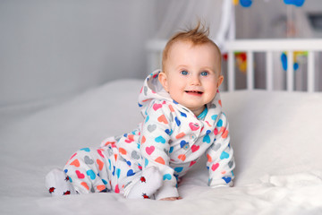 Cute smiling baby sitting on the white blanket at the bed