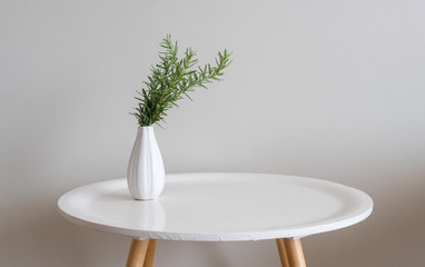 Sprigs of rosemary in small white vase on round table against beige wall