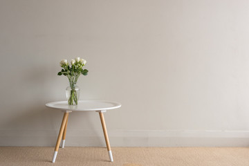 White roses in glass vase  on small round table against beige wall
